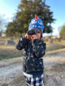 little girl peering through a scope